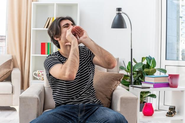 Jonge man in vrijetijdskleding schreeuwend met handen in de buurt van mond zittend op de stoel in lichte woonkamer living