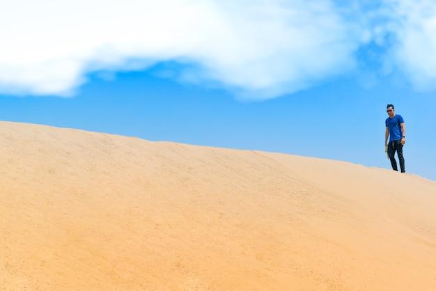 Jonge man in vrijetijdskleding vooruit lopen in de woestijn