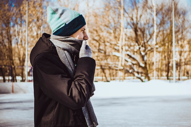 Jonge man in warme kleding en sjaal op een winterdag