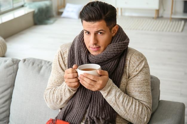 Jonge man in warme kleren en met een kopje thee thuis. concept van het stookseizoen
