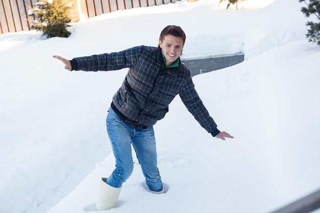Jonge man in winter laarzen viel in een diepe witte sneeuw