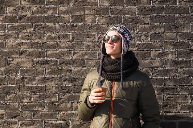 Jonge man in winterkleren houdt kopje koffie