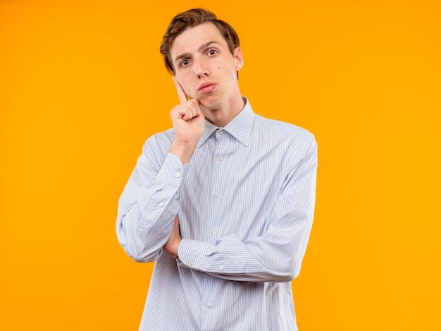 Jonge man in wit overhemd camera kijken met peinzende uitdrukking uitdrukking op gezicht staande over oranje achtergrond