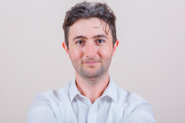 Jonge man in wit overhemd die naar de camera kijkt en er gelukkig uitziet
