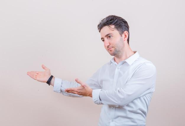 Jonge man in wit overhemd doet welkomstgebaar en ziet er vriendelijk uit