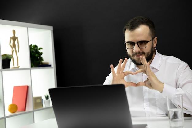 Jonge man in wit overhemd en bril communiceert online met vrienden en familie