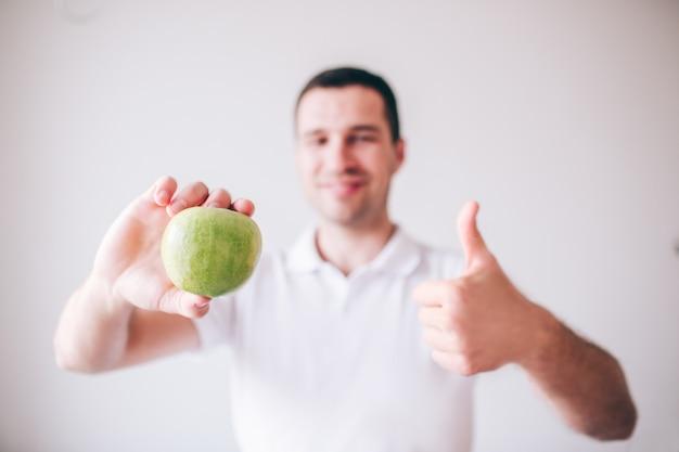 Jonge man in wit overhemd geïsoleerd op achtergrond. de kerel houdt groene appel in hand en glimlacht. toon grote duim omhoog. lekker lekker fruit.