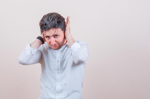 Jonge man in wit overhemd hand in hand op oren en geïrriteerd?