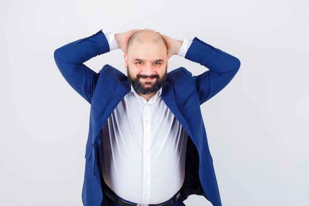 Jonge man in wit overhemd, jas hand in hand achter het hoofd en ziet er ontspannen uit, vooraanzicht.
