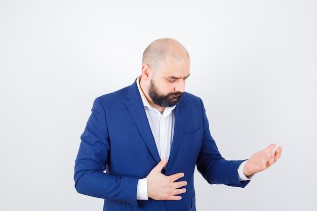 Jonge man in wit overhemd, jas kijkend naar zijn lege handpalm en verdrietig, vooraanzicht.