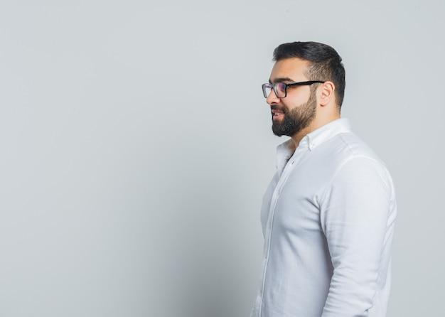 Jonge man in wit overhemd kijken naar de voorkant oh hem en peinzend kijken.