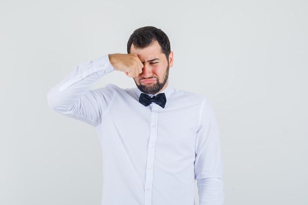 Jonge man in wit overhemd oog wrijven terwijl huilen, vooraanzicht.