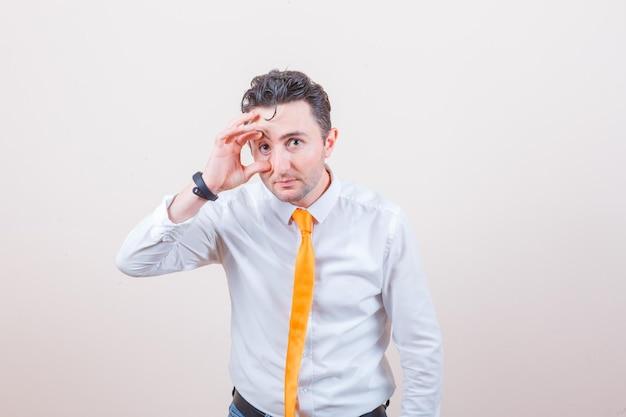 Jonge man in wit overhemd, stropdas die oog opent met vingers en er moe uitziet