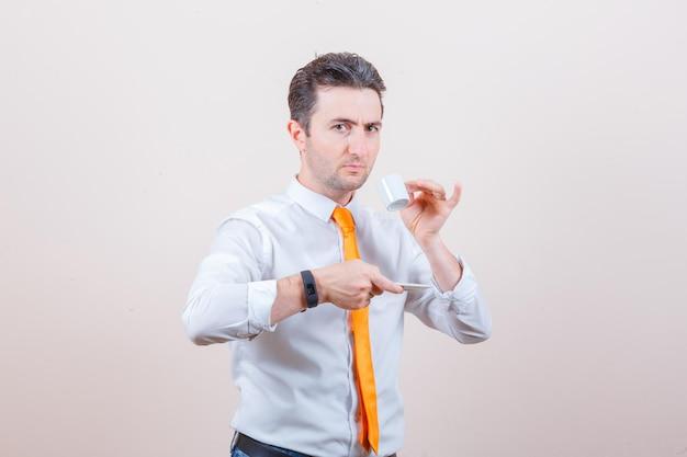 Jonge man in wit overhemd, stropdas die turkse koffie drinkt en peinzend kijkt