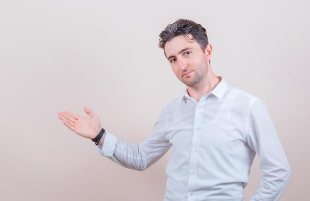 Jonge man in wit overhemd verwelkomt of laat iets zien en ziet er vriendelijk uit Gratis Foto