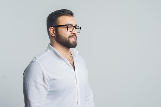 Jonge man in wit overhemd wegkijken terwijl glimlachend en elegant kijken.