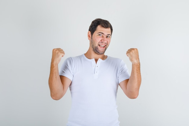 Jonge man in wit t-shirt balde vuisten en glimlachen en kijken gelukkig