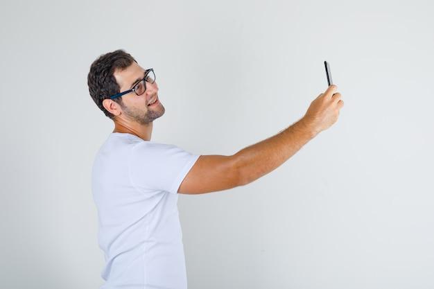 Jonge man in wit t-shirt, bril selfie op smartphone te nemen en op zoek vrolijk