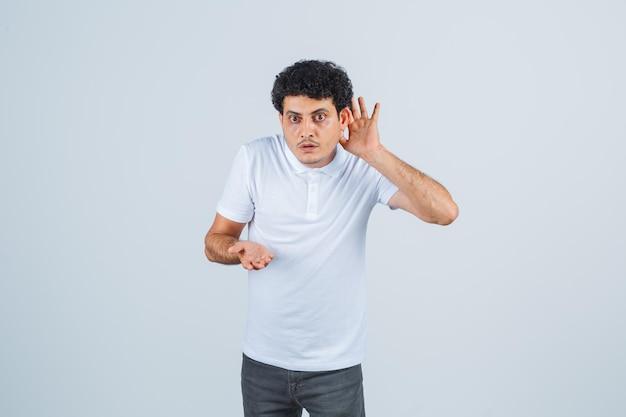 Jonge man in wit t-shirt, broek die hand achter het oor houdt en nieuwsgierig kijkt, vooraanzicht.