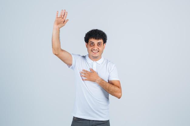 Jonge man in wit t-shirt, broek die met de hand zwaait om afscheid te nemen en er vrolijk uitziet, vooraanzicht.