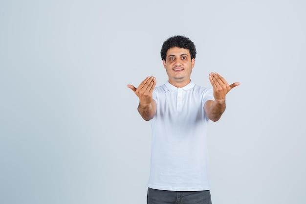 Jonge man in wit t-shirt, broek die uitnodigt om te komen en er zelfverzekerd uitziet, vooraanzicht.