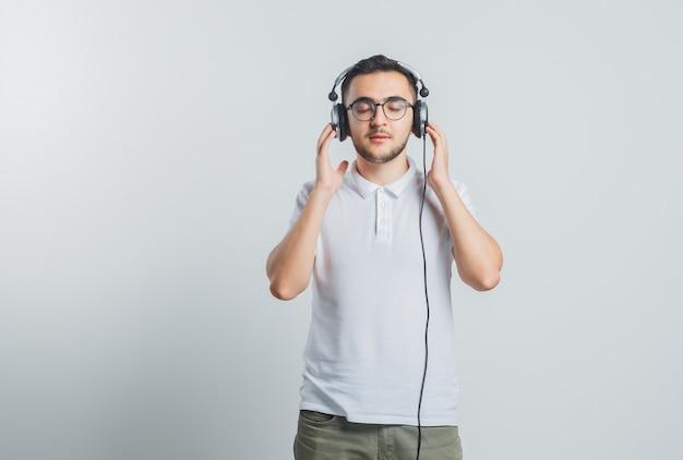Jonge man in wit t-shirt, broek genieten van muziek met koptelefoon en op zoek ontspannen