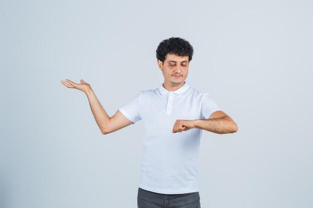 Jonge man in wit t-shirt, broek kijkend naar horloge deed alsof hij gedragen was en zag er zelfverzekerd uit, vooraanzicht.