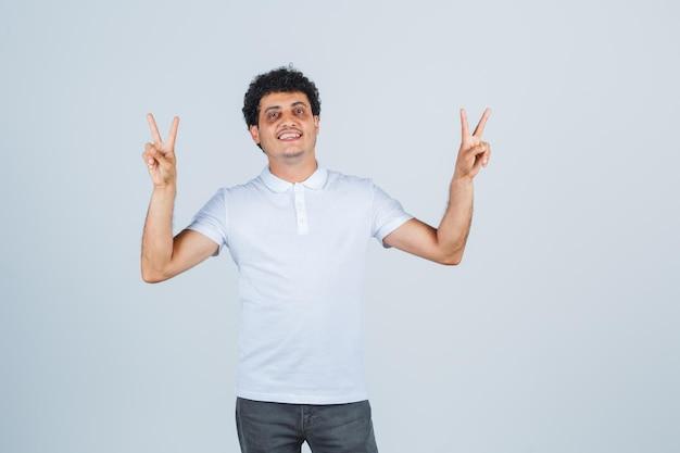 Jonge man in wit t-shirt, broek met overwinningsgebaar en zelfverzekerd, vooraanzicht.