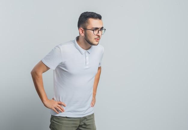 Jonge man in wit t-shirt, broek wegkijken met handen op taille en op zoek gericht
