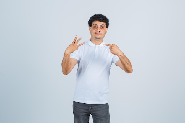 Jonge man in wit t-shirt, broek wijzend op nummer drie en zelfverzekerd, vooraanzicht.