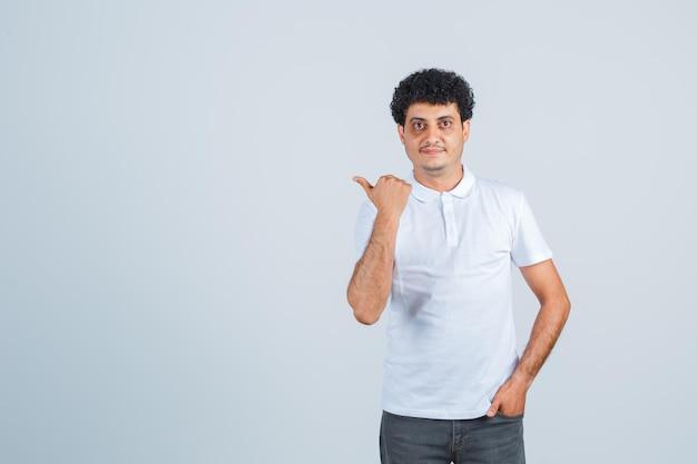 Jonge man in wit t-shirt en spijkerbroek die de hand in de zak steekt terwijl hij wegwijst en er serieus uitziet, vooraanzicht.