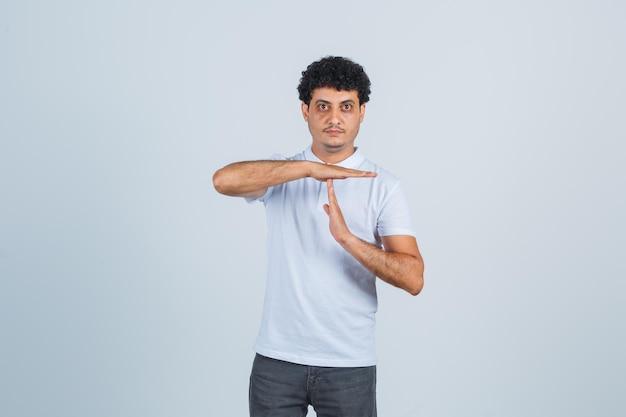 Jonge man in wit t-shirt en spijkerbroek die een pauzegebaar toont en er serieus uitziet, vooraanzicht.