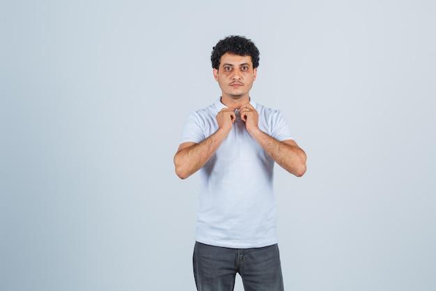 Jonge man in wit t-shirt en spijkerbroek die handen op de kraag zet en er serieus uitziet, vooraanzicht.