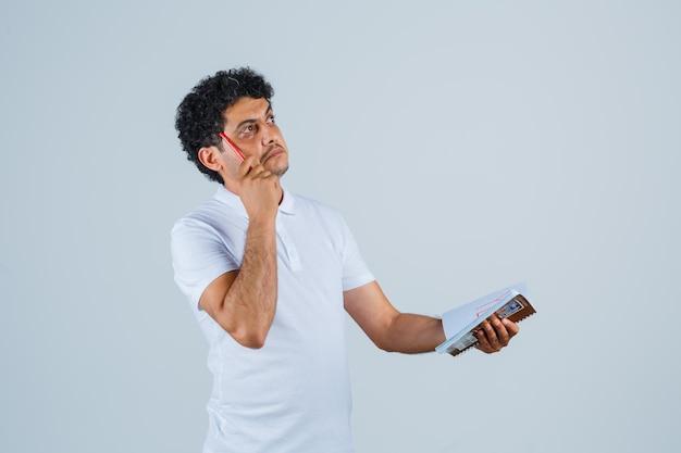 Jonge man in wit t-shirt en spijkerbroek die pen bijt, notitieboekje vasthoudt en aan iets denkt en peinzend kijkt, vooraanzicht.