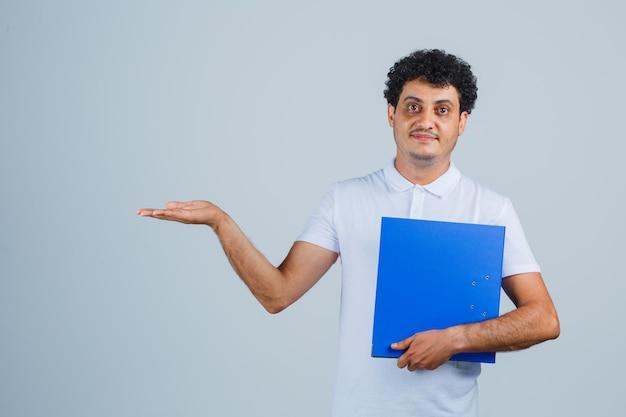 Jonge man in wit t-shirt en spijkerbroek met bestandsmap, handpalm uitrekkend en gelukkig, vooraanzicht.