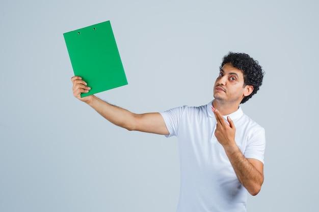 Jonge man in wit t-shirt en spijkerbroek met notitieboekje en pen, denkend aan iets en peinzend kijkend, vooraanzicht.