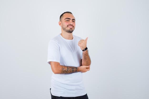 Jonge man in wit t-shirt en zwarte broek die duim opsteekt en er gelukkig uitziet