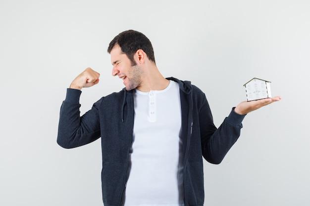 Jonge man in wit t-shirt en zwarte hoodie met rits aan de voorkant met huismodel in de ene hand, de pose van de winnaar toont en optimistisch kijkt, vooraanzicht.
