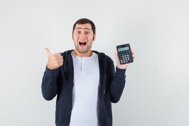 Jonge man in wit t-shirt en zwarte hoodie met rits aan de voorkant met rekenmachine en duim opdagen en op zoek naar optimistisch, vooraanzicht.