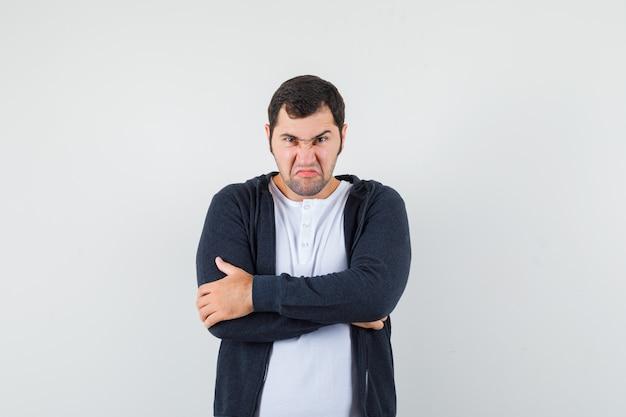 Jonge man in wit t-shirt en zwarte hoodie met rits vooraan staande armen gekruist en op zoek boos, vooraanzicht.