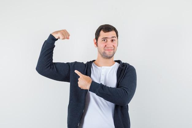 Jonge man in wit t-shirt en zwarte hoodie met ritssluiting die spieren met wijsvinger richt en optimistisch, vooraanzicht kijkt.