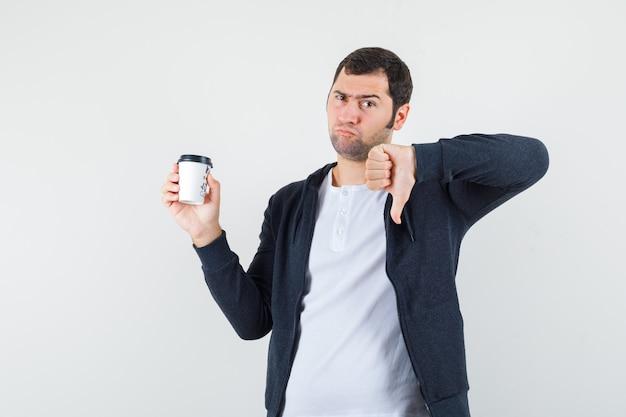 Jonge man in wit t-shirt en zwarte hoodie met ritssluiting en afhaalmaaltijden koffiekopje te houden en duim naar beneden te tonen en ontevreden, vooraanzicht te kijken.