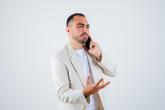 Jonge man in wit t-shirt, jas die met de telefoon praat en de hand uitstrekt als iets vast te houden en er serieus uit te zien, vooraanzicht.