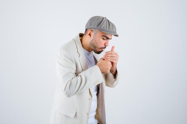 Jonge man in wit t-shirt, jas en grijze pet die sigaretten rookt en er gefocust uitziet