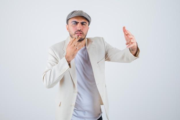 Jonge man in wit t-shirt, jas en grijze pet die sigaretten rookt en hand naar voren strekt en boos kijkt