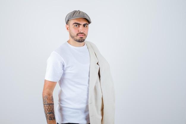 Jonge man in wit t-shirt, jas en grijze pet poseren vooraan met jas op schouder en kijken serieus