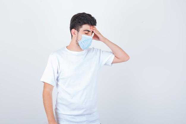 Jonge man in wit t-shirt, masker dat lijdt aan hoest en er moe uitziet