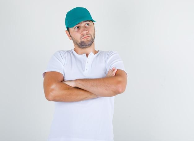 Jonge man in wit t-shirt met pet denken met gekruiste armen