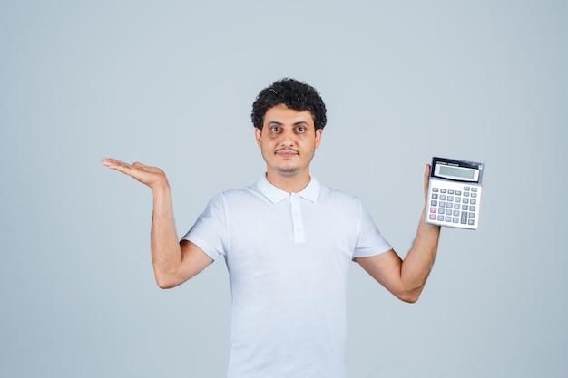 Jonge man in wit t-shirt met rekenmachine terwijl hij de palm opzij spreidt en er zelfverzekerd uitziet, vooraanzicht.