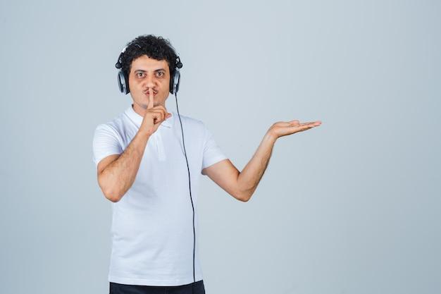 Jonge man in wit t-shirt met stiltegebaar, palm opzij spreidend en verstandig, vooraanzicht.
